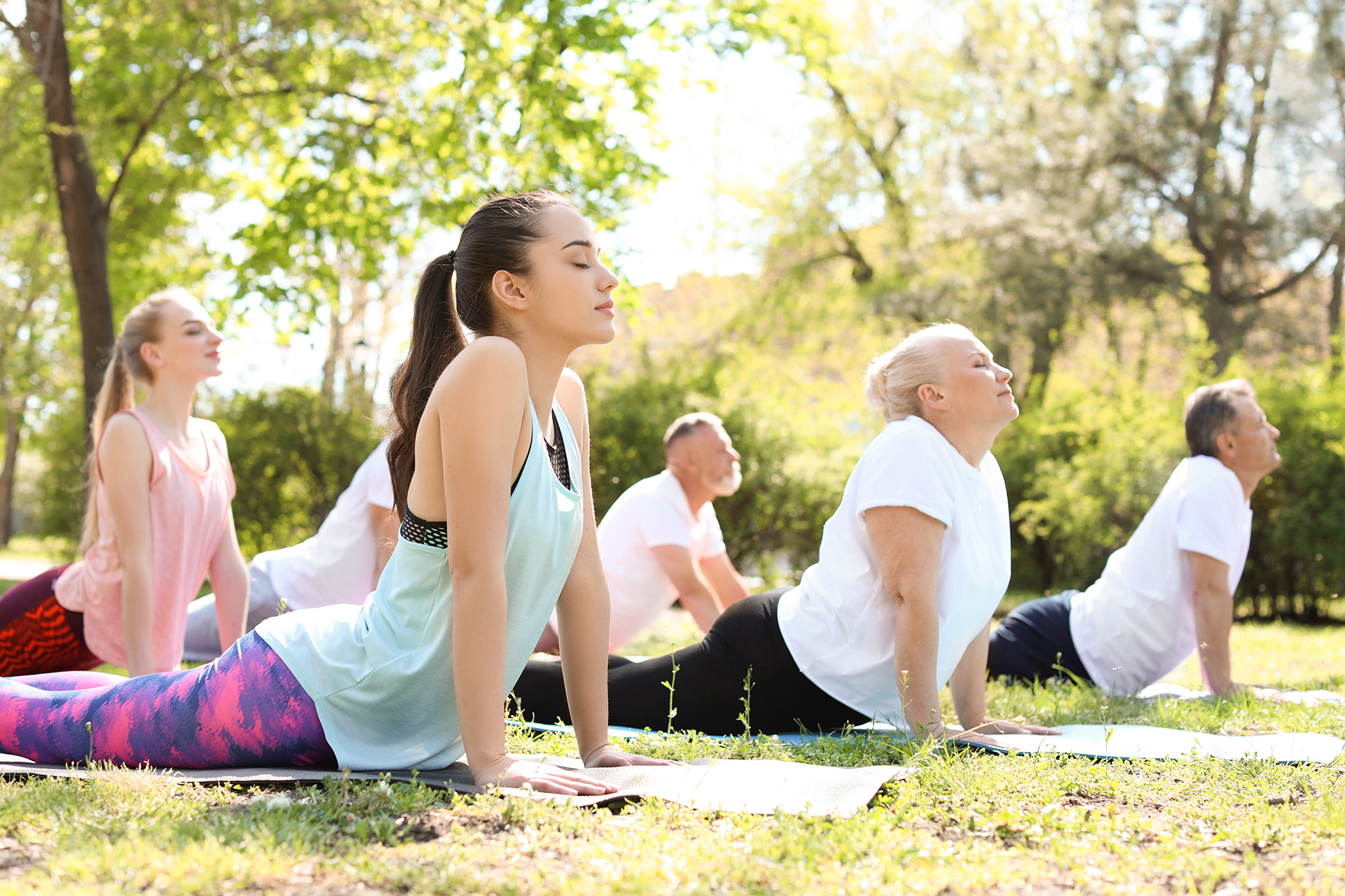 Group of people practicing yoga in park on sunny day