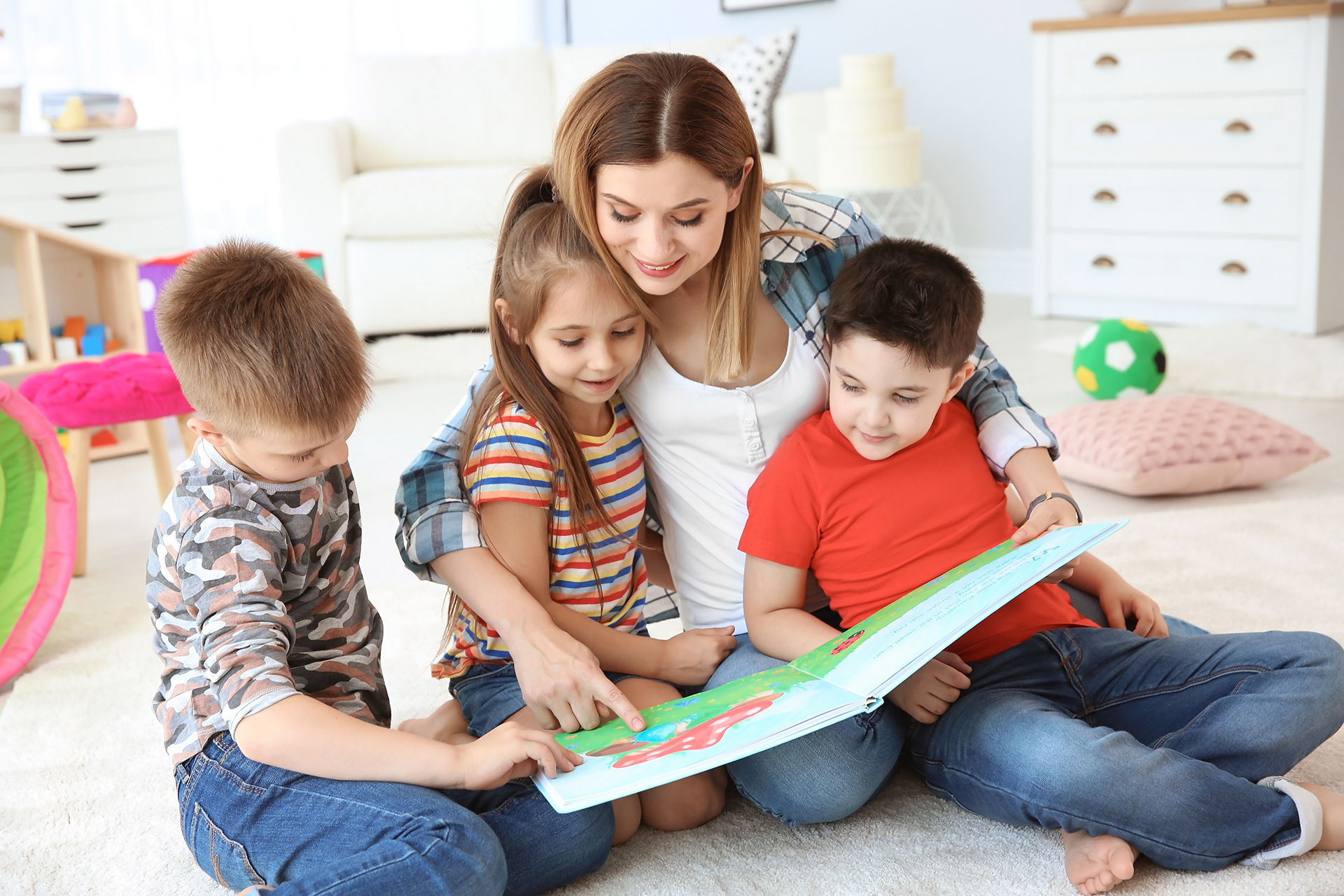 Cute little children reading book on floor with young mother in