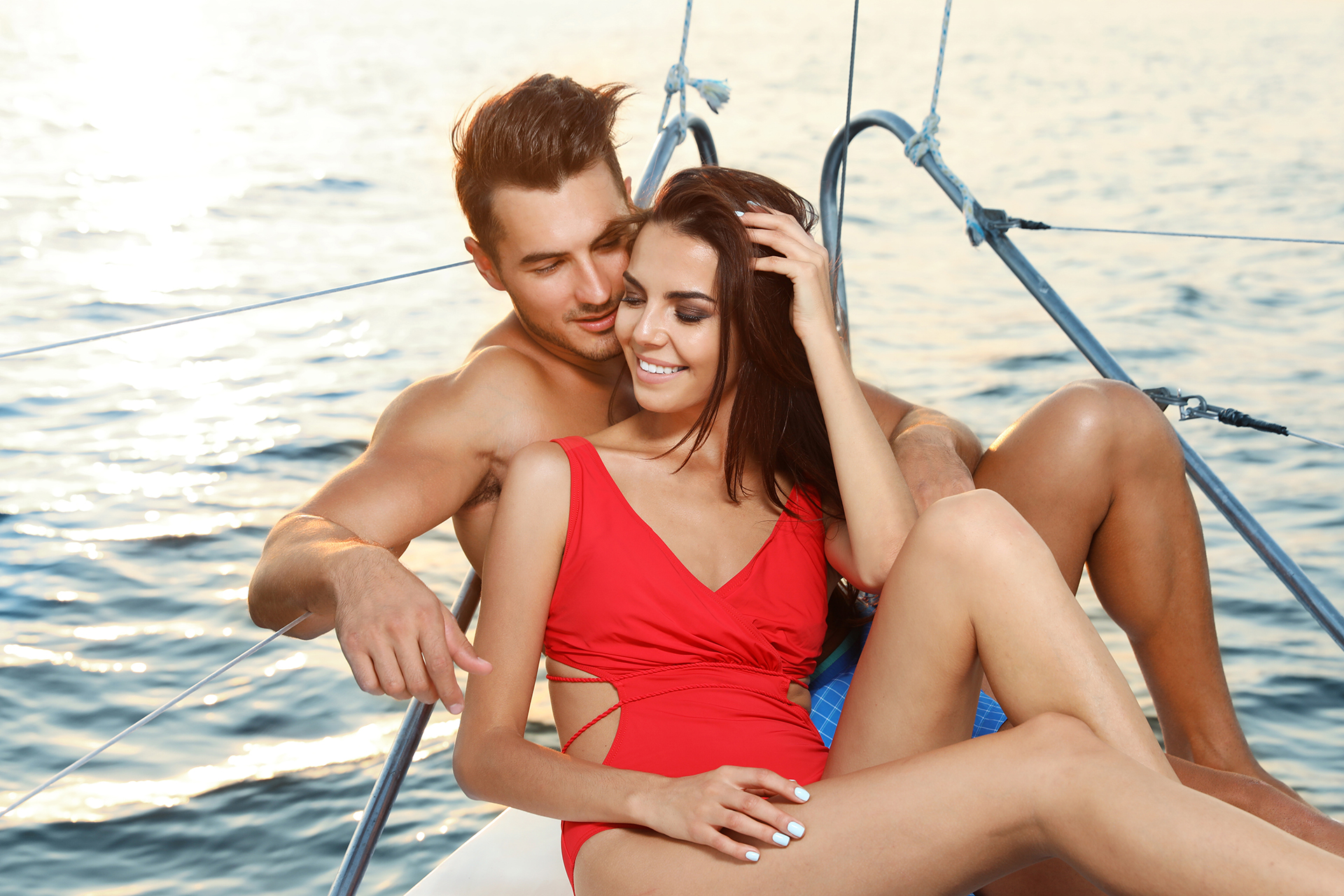 Young man and his beautiful girlfriend in bikini on yacht. Happy