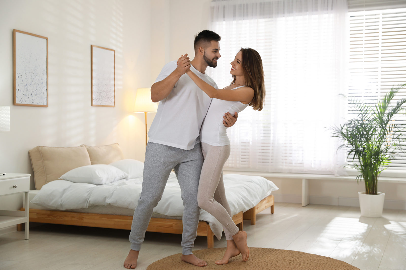 Lovely young couple dancing in bedroom at home