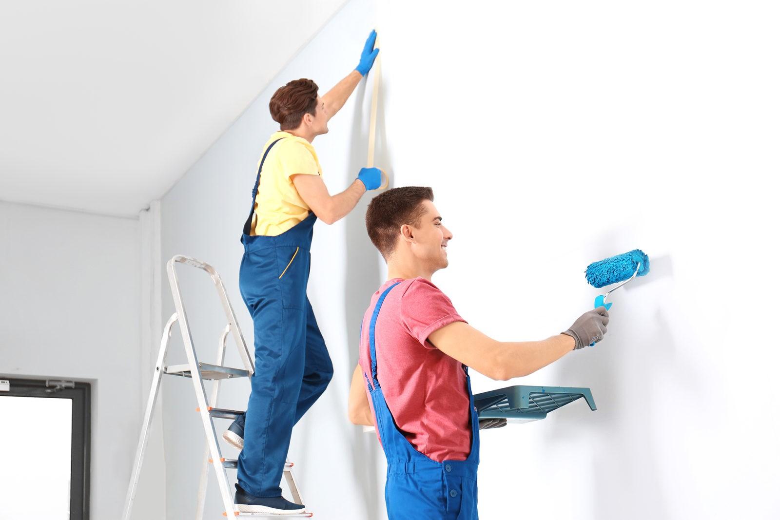 Male decorators refurbishing empty room