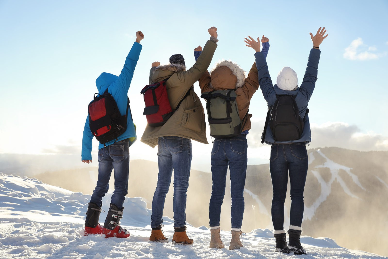 Group of excited friends with backpacks enjoying mountain view during winter vacation