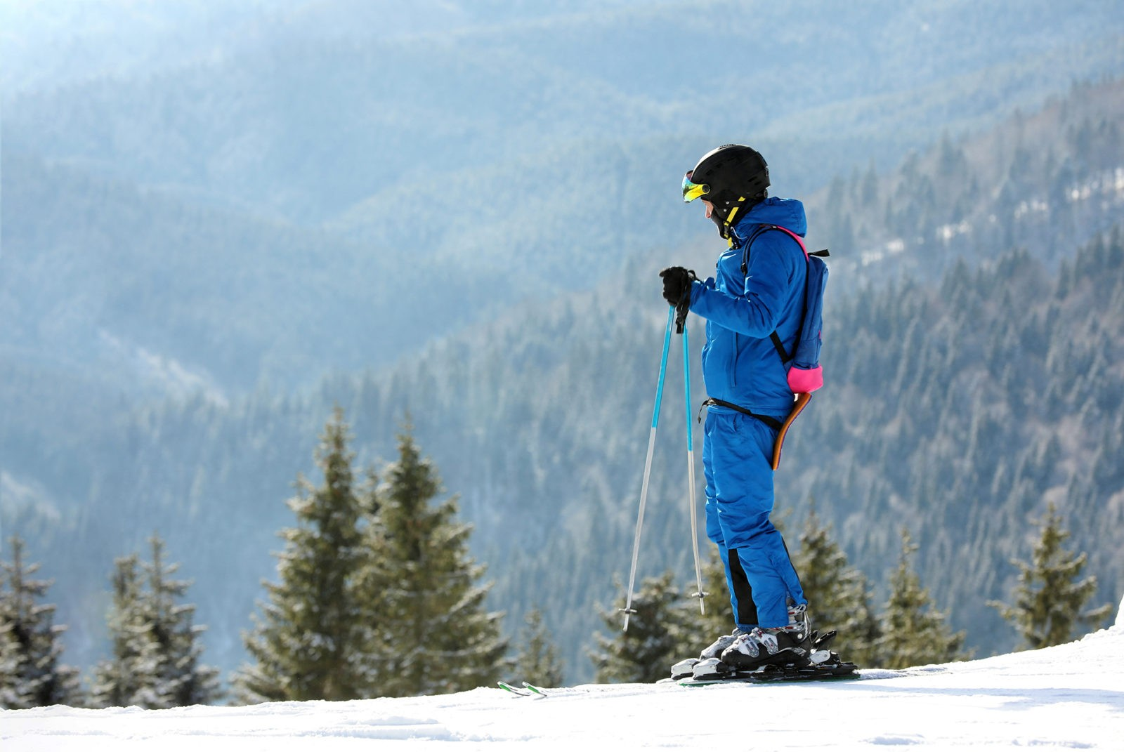 Man skiing on snowy hill in mountains, space for text. Winter vacation