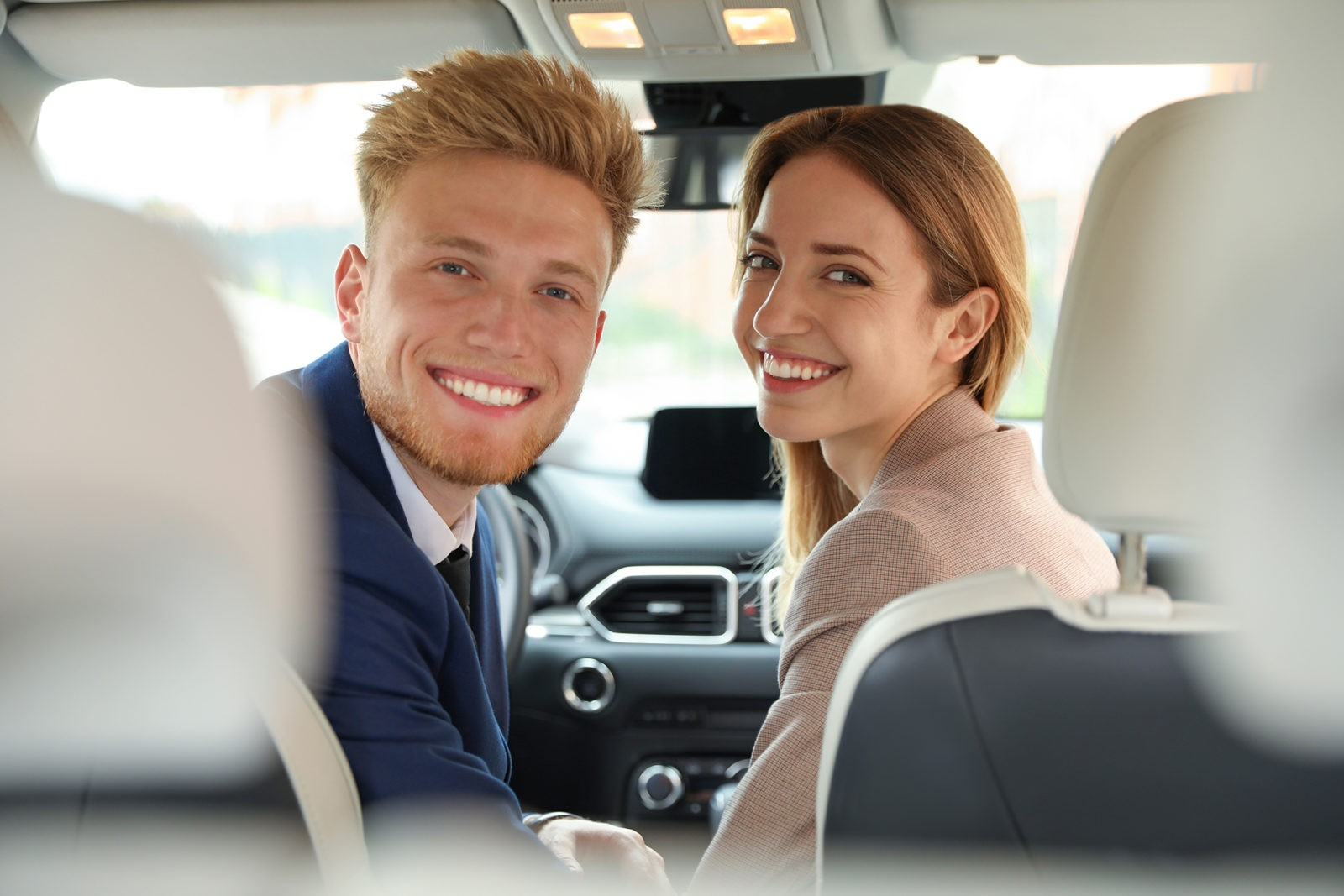 Happy young man and woman in modern car
