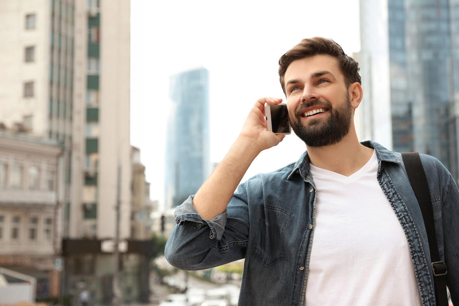 Handsome man talking on phone in modern city