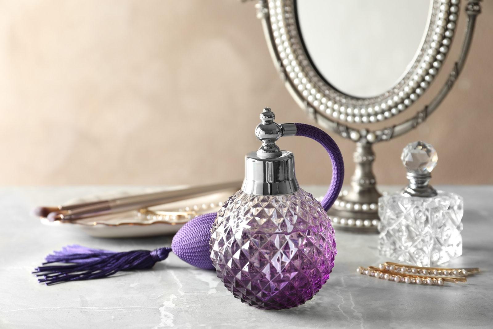 Different elegant perfume bottles on dressing table