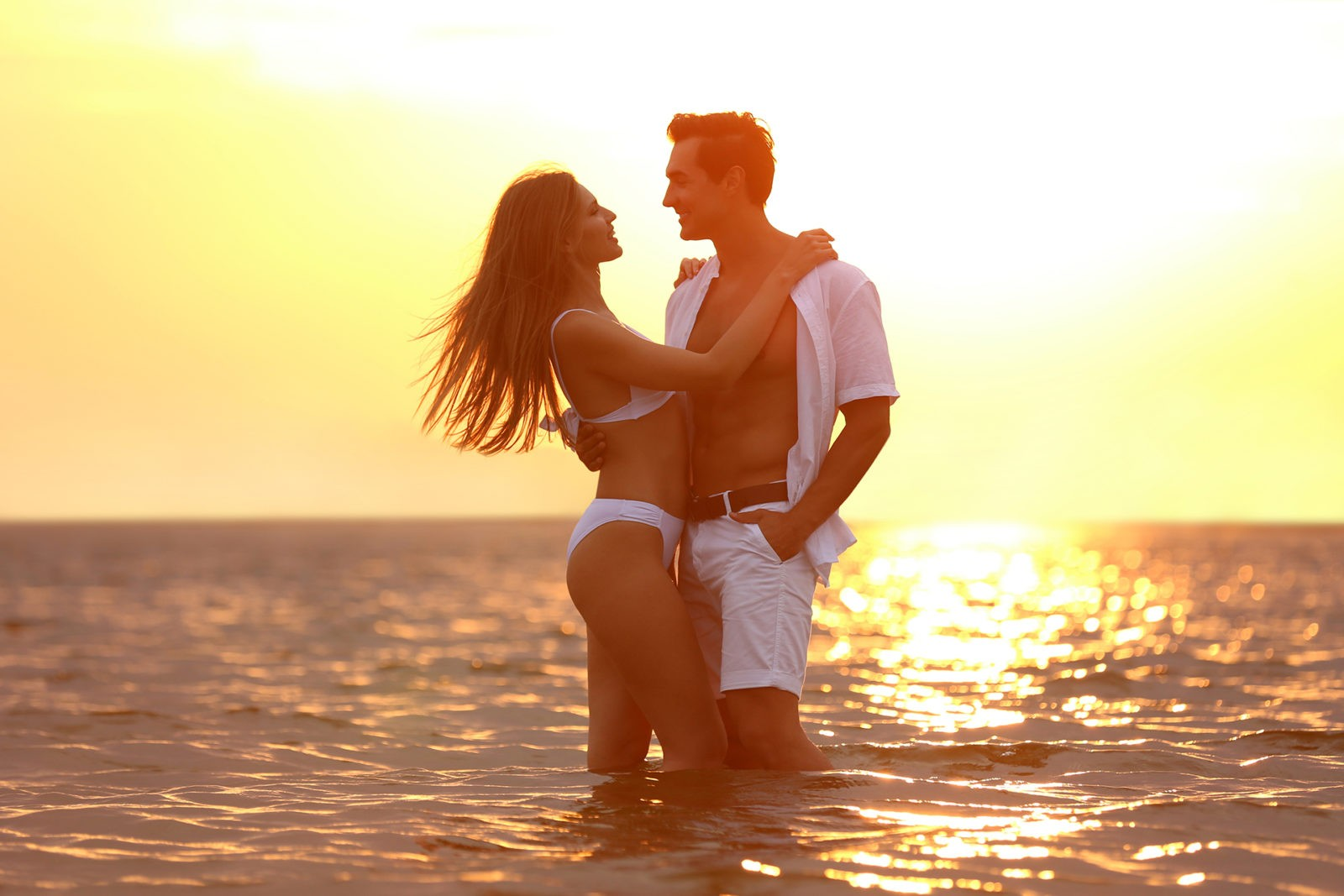 Happy young couple spending time together on sea beach at sunset