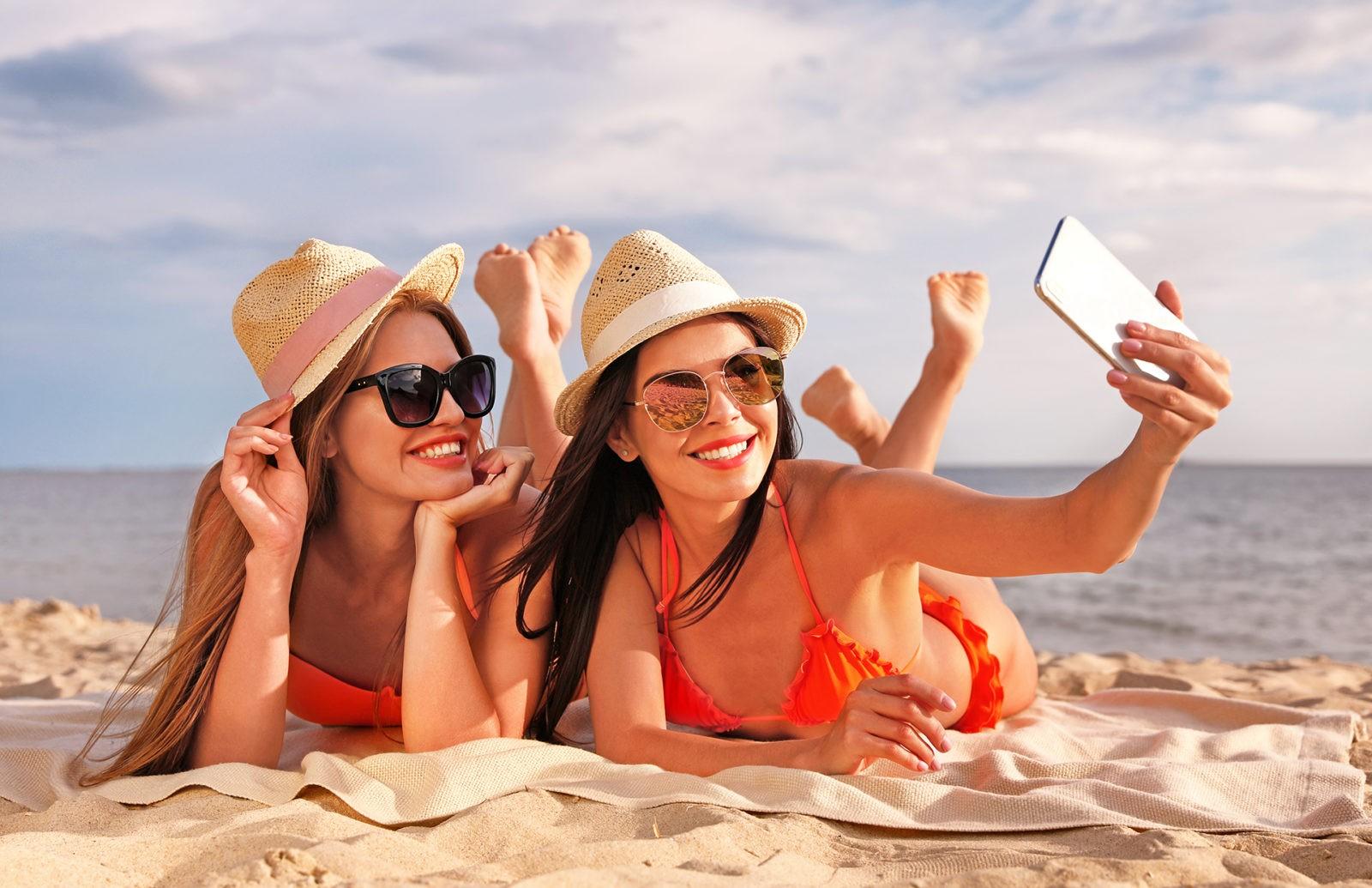 Young couple in bikini taking selfie on beach