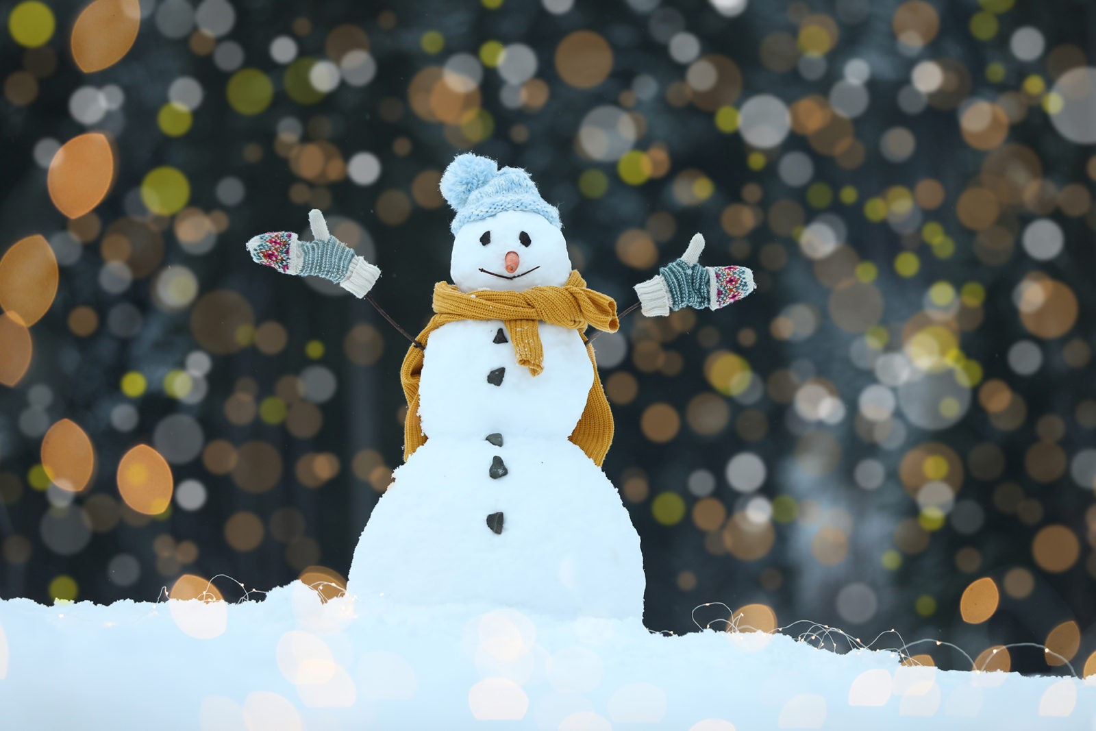 Adorable smiling snowman and blurred Christmas lights on background outdoors. Winter day