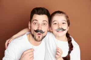Dad and his daughter having fun on color background. Father's day celebration