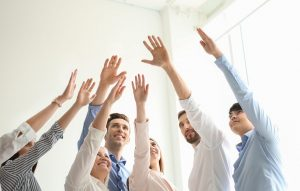 People raising hands together indoors. Unity concept