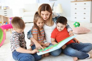 Cute little children reading book on floor with young mother in playing room