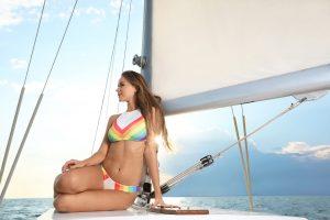 Beautiful young woman in bikini sitting on yacht at sea