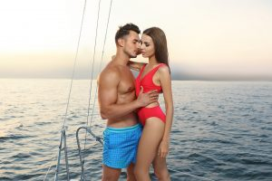 Young man and his beautiful girlfriend in bikini on yacht. Happy couple during sea trip