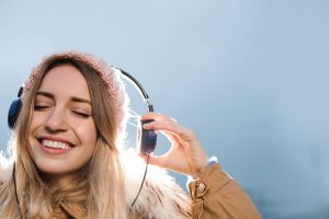 Young woman with headphones listening to music outdoors. Space for text