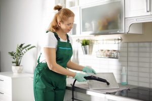 Professional janitor cleaning mesh filter of cooker hood in kitchen