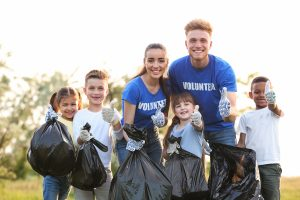 Volunteers and kids with bags of trash in park
