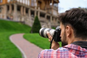Photographer taking photo of beautiful house with professional camera outdoors