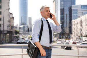 Handsome businessman talking by mobile phone in city