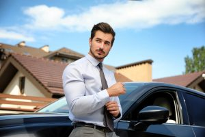 Attractive young man near luxury car outdoors