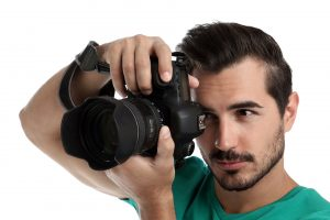 Young professional photographer taking picture on white background