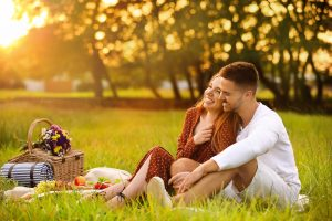Happy young couple having picnic in park