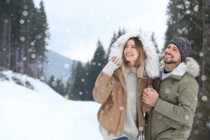 Happy couple near conifer forest on snowy day, space for text. W