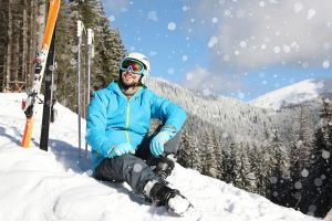Man with ski equipment sitting on snow in mountains, space for t