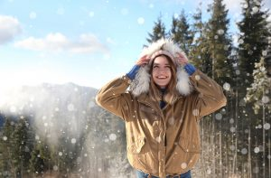 Happy young woman spending winter vacation in mountains. Space for text