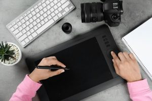 Female designer working with graphic tablet at grey stone table