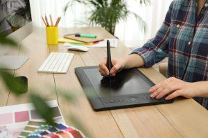 Professional designer working on graphic tablet at desk, closeup
